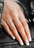 Artificial fingernails. Hand of caucasian woman with long artificial fingernails over black leather handbag or purse Stock Images