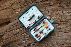 Artificial flies. For fly fishing outdoors on a log royalty free stock photo