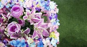 Artificial flower boquet. And green grass background stock photos