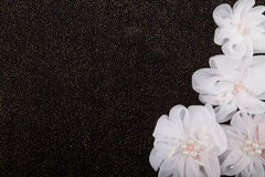 Artificial flowers on black background. With golden sequins Royalty Free Stock Photo