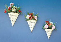 Artificial flowers on blue wall Stock Photography