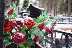 Artificial flowers bouquet of roses on the grave in the winter. Cemetery decorations. Selective focus Royalty Free Stock Image