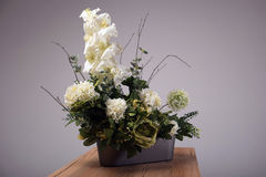 Artificial flowers bouquet in vase on the table Stock Photography