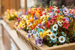 Artificial flowers in the box outside the window. Selective focus, copy space royalty free stock photo