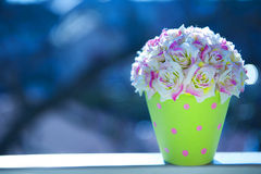 Artificial flowers. Colorful plastic flower vase. Flower garden view window. White with pink roses, green polka dot vase Stock Photo