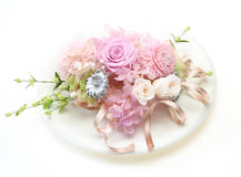 Artificial flowers on a dish Stock Image