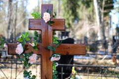Artificial flowers garland or wreath of roses on the cross on the grave in the spring. Cemetery decorations. Royalty Free Stock Images