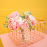Artificial flowers on pink table. Pastel Stock Photo