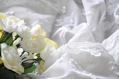 Artificial Flowers on White Chiffon Fabric Background Stock Images
