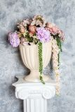 Artificial flowers in vase on the greek column Stock Photo