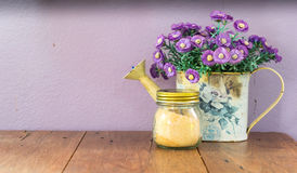 Artificial flowers in vase with sugar jar on table stock images