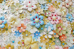 Artificial flowers on the wall. With colorful stock images
