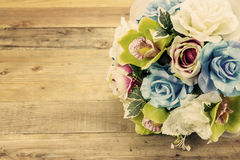 Artificial flowers on wooden background, Vintage effect. Close up Artificial flowers on wooden background, Vintage effect Stock Photos