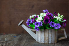 Artificial flowers on wooden table Stock Image