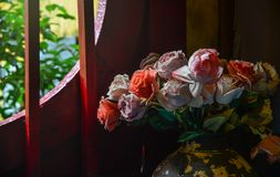Artificial flowers with the wooden window stock photo