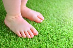 Artificial grass background. Tender foots of a baby on a green artificial turf. royalty free stock photos