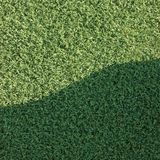 Artificial grass fake turf lawn texture field. Artificial grass fake astro turf synthetic lawn field macro closeup with gentle shaded shadow area, green sports Royalty Free Stock Images