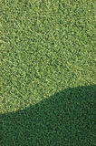 Artificial grass fake turf synthetic lawn field macro closeup with gentle shaded shadow area, green sports texture background Stock Image