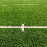 Artificial grass field on football playground. Detail of a cross of painted white lines in a soccer field. Plastic grass Stock Image