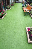 Artificial grass for garden walkways Stock Photography