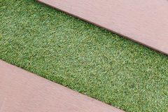 Artificial grass with wood floor texture backgroud Royalty Free Stock Images