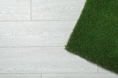 Artificial grass on wooden background, top view. With space for text stock photography
