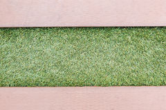 Artificial grass with wooden texture backgroud Stock Image