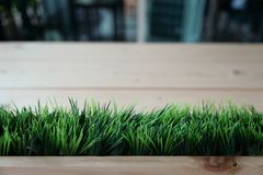 Artificial green grass arranged in the horizontal row at the front of plank wooden table blur background stock images
