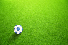 Artificial green grass with blue ball Royalty Free Stock Image