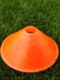 Artificial green plastic grass in background with  bright orange plastic cone. Mark on winter footbal playground. Stock Images