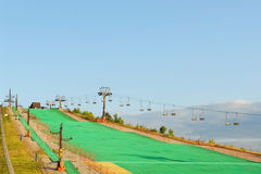Artificial green ski slope. With ski lift, blue sky background Stock Photo