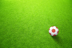 Artificial green soccerfield with red ball Stock Photos