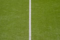 Artificial green turf texture background with white line marks.  royalty free stock image
