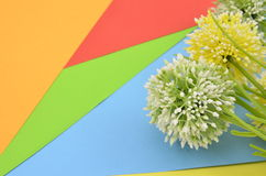 Artificial green and yellow flower on blue,green,red,orange and yellow background Stock Photos