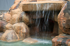 An artificial grotto with a waterfall. Royalty Free Stock Image
