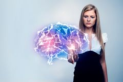 Artificial intelligence concept. Attractive young woman pointing at abstract glowing polygonal brain. Artificial intelligence concept Royalty Free Stock Image