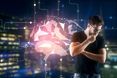 Artificial intelligence concept. Thoughtful young businessman with abstract polygonal brain interface standing on blurry night city background. Artificial Stock Photography