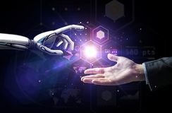 Robot and human hand over virtual projection. Artificial intelligence, future technology and business concept - robot and human hand with flash light and virtual royalty free stock image