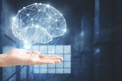 Artificial intelligence and science concept. Hand holding glowing polygonal brain on blurry interior background. Artificial intelligence and science concept. 3D Stock Images