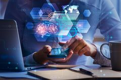 Artificial intelligence and technology concept. Close up of businesswoman hands using smartphone and office desk with laptop, coffee cup, notepad and abstract royalty free stock photo