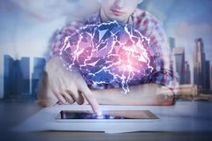 Artificial intelligence and technology concept. Young man using tablet with polygonal brain hologram on blurry city background. Artificial intelligence and royalty free stock photography