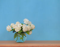 The artificial jasmine flower in the pot at the wood table with stock photo