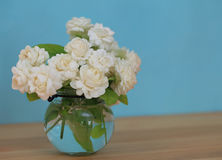 The artificial jasmine flower in the pot at the wood table with royalty free stock image