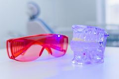 The artificial jaw lies next to the glasses on the table. An artificial jaw lies next to the glasses stock image