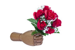 Artificial Love. Artificial Wooden Hand holding Artificial Flowers Isolated on White Stock Image