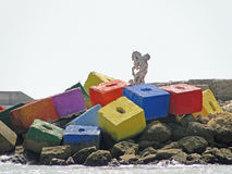 Artificial marine reef with colorful stones. The breakwater is decorated with different colors ua statue patron of sailors Royalty Free Stock Photos