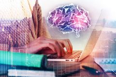 Artificial mind concept. Side view of female hands using laptop at workplace with abstract polygonal brain hologram and city view. Artificial mind concept Stock Image