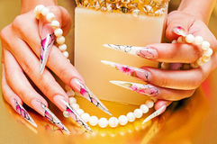 Artificial nails and pearls Stock Photos