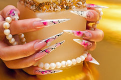 Artificial nails and pearls. Hands with artificial nails and pearls Royalty Free Stock Image