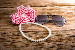 Artificial pearl necklace and sunglasses, Hair bow Royalty Free Stock Images